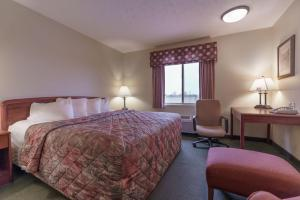A bed or beds in a room at Supertel Inn & Conference Center