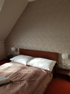 A bed or beds in a room at Amaretto Szállás