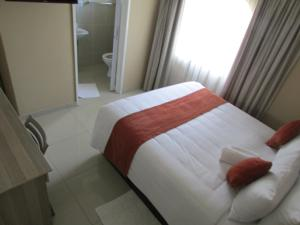 A bed or beds in a room at Bridgeville Guest House( Pty) Ltd