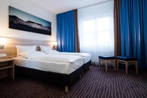 A bed or beds in a room at AMBER ECONTEL Berlin Charlottenburg