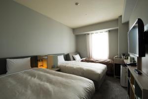 A bed or beds in a room at HOTEL FUKURACIA OSAKA-BAY