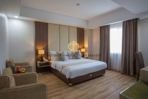 A bed or beds in a room at Orchardz Hotel Bandara