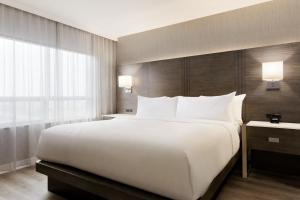 A bed or beds in a room at Embassy Suites By Hilton Toronto Airport