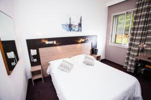 A bed or beds in a room at Aeroport Hotel - Parc Expo