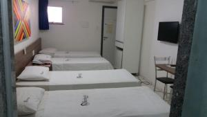 A bed or beds in a room at Sambura Hotel