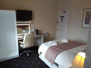 A bed or beds in a room at Dalgair House Hotel