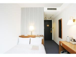 A bed or beds in a room at Smile Hotel Nihombashi Mitsukoshimae