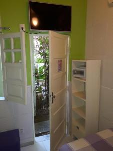 Uma TV ou centro de entretenimento em Hotel Pousada Papaya Verde