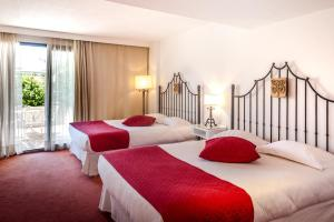 A bed or beds in a room at Avignon Grand Hotel