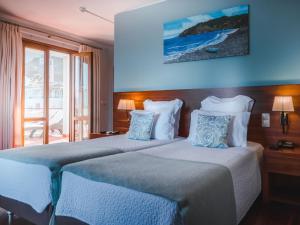 A bed or beds in a room at Hotel Vila Bela