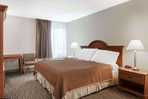 A bed or beds in a room at Travelodge by Wyndham Little Falls
