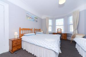 A bed or beds in a room at Sandy Bay Guest House