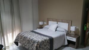 A bed or beds in a room at Hostal Tilos