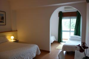 A bed or beds in a room at Guest House Oliveira