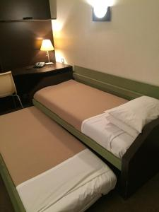A bed or beds in a room at At Home Appart Hotel