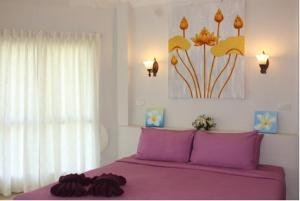 A bed or beds in a room at Nimmanoradee Resort - SHA Certified
