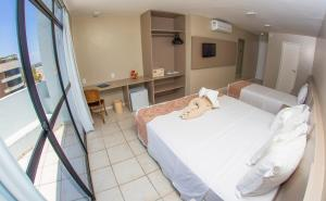 A bed or beds in a room at Maceió Mar Hotel