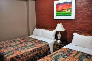 A bed or beds in a room at Hotel Ste-Catherine