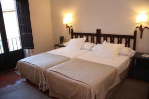 A bed or beds in a room at Parador de Ávila