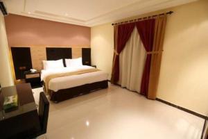 Cama ou camas em um quarto em توليب الروضة للشقق الفندقية