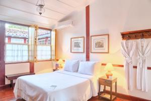A bed or beds in a room at Pousada do Ouro