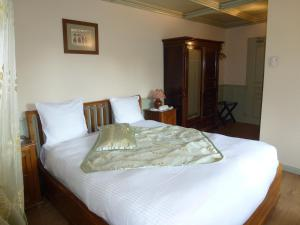A bed or beds in a room at La Cour du Bailli Suites & Spa