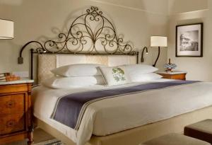 A bed or beds in a room at Monastero Santa Rosa Hotel & Spa