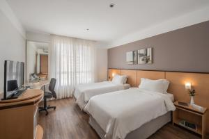 A bed or beds in a room at Intercity Caxias do Sul