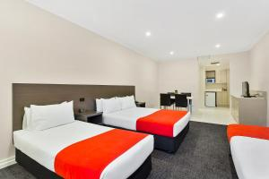 A bed or beds in a room at Quality Hotel Manor