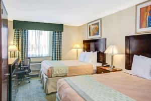 A bed or beds in a room at Hillcrest Hotel Near JFK Airtrain