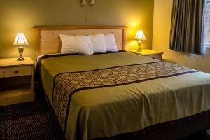 A bed or beds in a room at Green Gables Motel & Suites