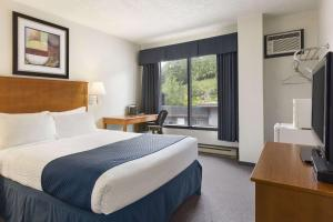 A bed or beds in a room at Days Inn by Wyndham Kenora