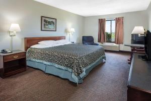 A bed or beds in a room at Days Inn by Wyndham Pontoon Beach