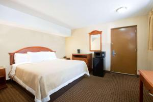 A bed or beds in a room at Days Inn by Wyndham Long Island/Copiague