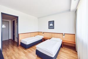 A bed or beds in a room at Sport- und Seminarhotel Hollabrunn