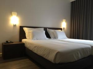 A bed or beds in a room at Hotel Euro Moniz