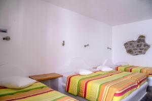 A bed or beds in a room at Paradise Beach Resort