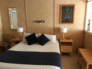 A bed or beds in a room at Tallow Beach Motel - Adults Only