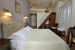 A bed or beds in a room at Dryades & Orion Hotel