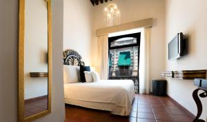 A bed or beds in a room at Hotel Herencia By Hosting House