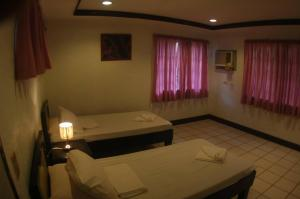 A bed or beds in a room at Mantangale Alibuag Dive Resort, Inc.