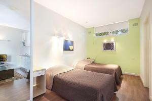 A bed or beds in a room at Ultimate Apartments Bondi Beach