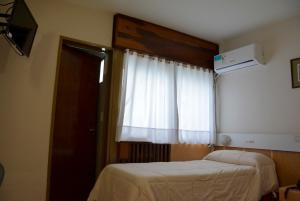 A bed or beds in a room at Hotel Menossi