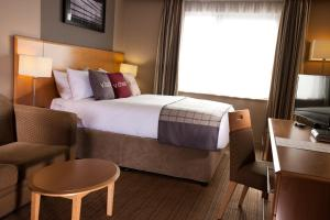A bed or beds in a room at Village Hotel Swansea