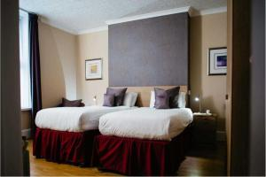 A bed or beds in a room at Hotel De Normandie