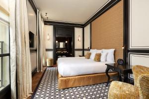 A bed or beds in a room at Le Pavillon de la Reine & Spa