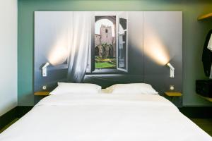 A bed or beds in a room at B&B Hôtel Narbonne (1)