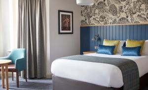A bed or beds in a room at The Bear Hotel by Greene King Inns