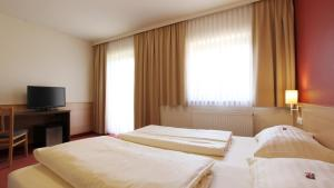 A bed or beds in a room at Familien Hotel Krainz