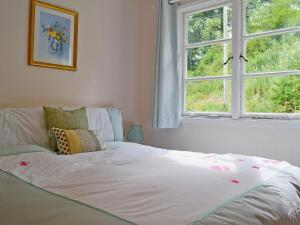 A bed or beds in a room at Benvane Cottage